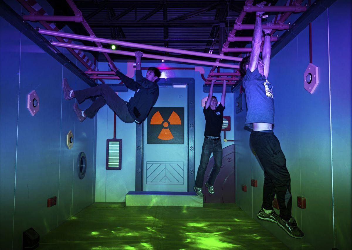 Three men dangle from monkey bars in a dark room with a radioactive symbol on a wall