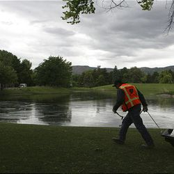 A hazmat crewman removes oil from the pond at Liberty Park after a Chevron pipeline broke and leaked oil, which flowed down into the park on Saturday.