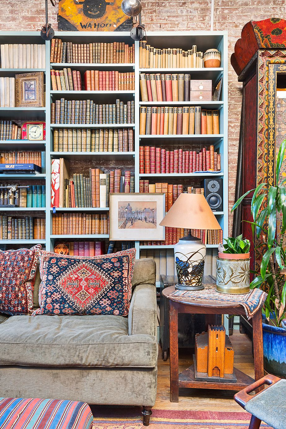 A large blue bookshelf behind a green couch.