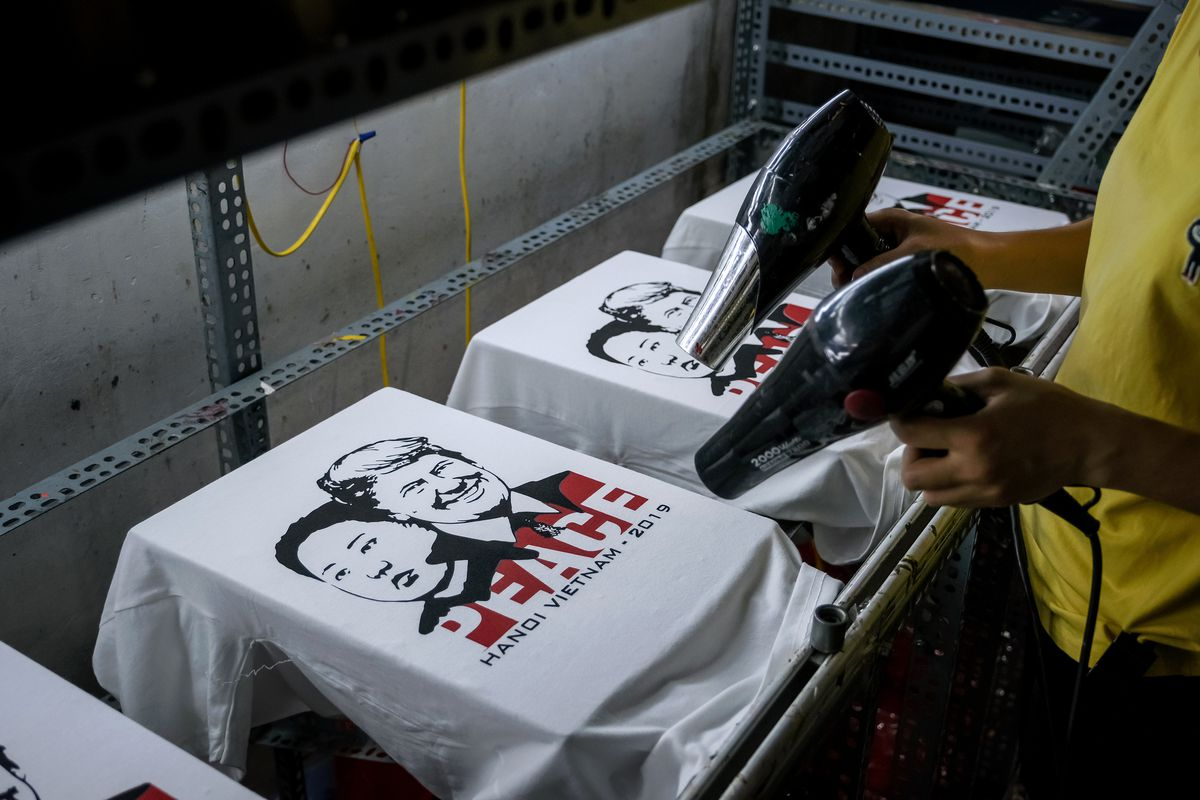 A worker at the t-shirt store of Truong Thanh Duc dry the newly printed t-shirts with the portraits of President Donald Trump and North Korean leader Kim Jong Un on February 21, 2019 in Hanoi, Vietnam.