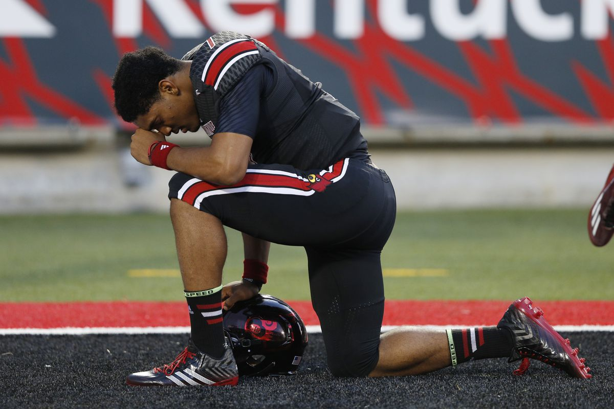 Reggie Bonnafon of the Louisville Cardinals kneels to pray in the end zone before a game against the Miami Hurricanes