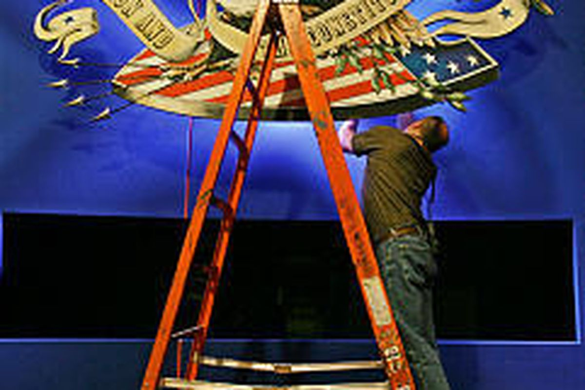 Stage technician Denis McCubbin adjusts a prop on a stage at Arizona State University, site of tonight's debate.