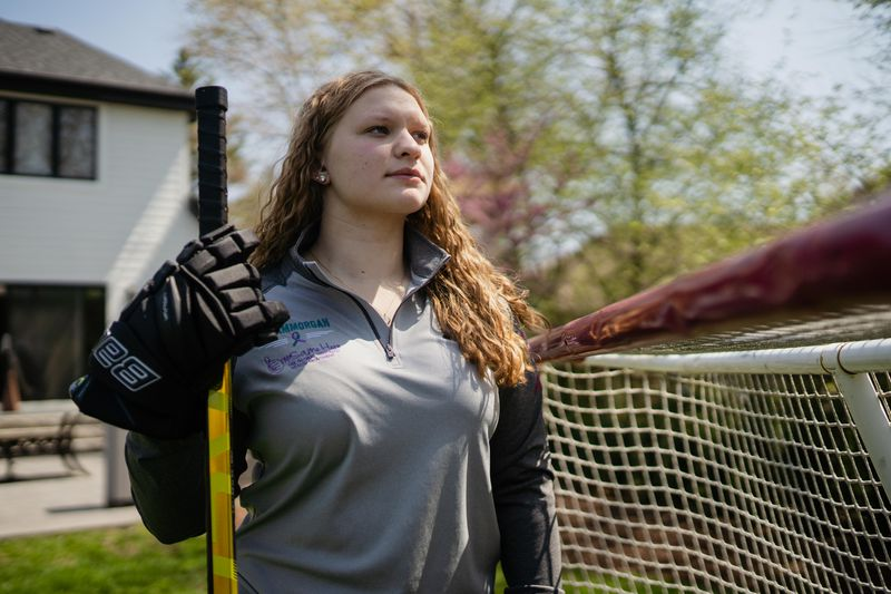 """Despite being able to rejoin the team, Morgan said from then on she was """"super uncomfortable"""" being alone with her coach and other players' parents. Morgan poses with hockey stick in hand in front of a goal in her backyard."""