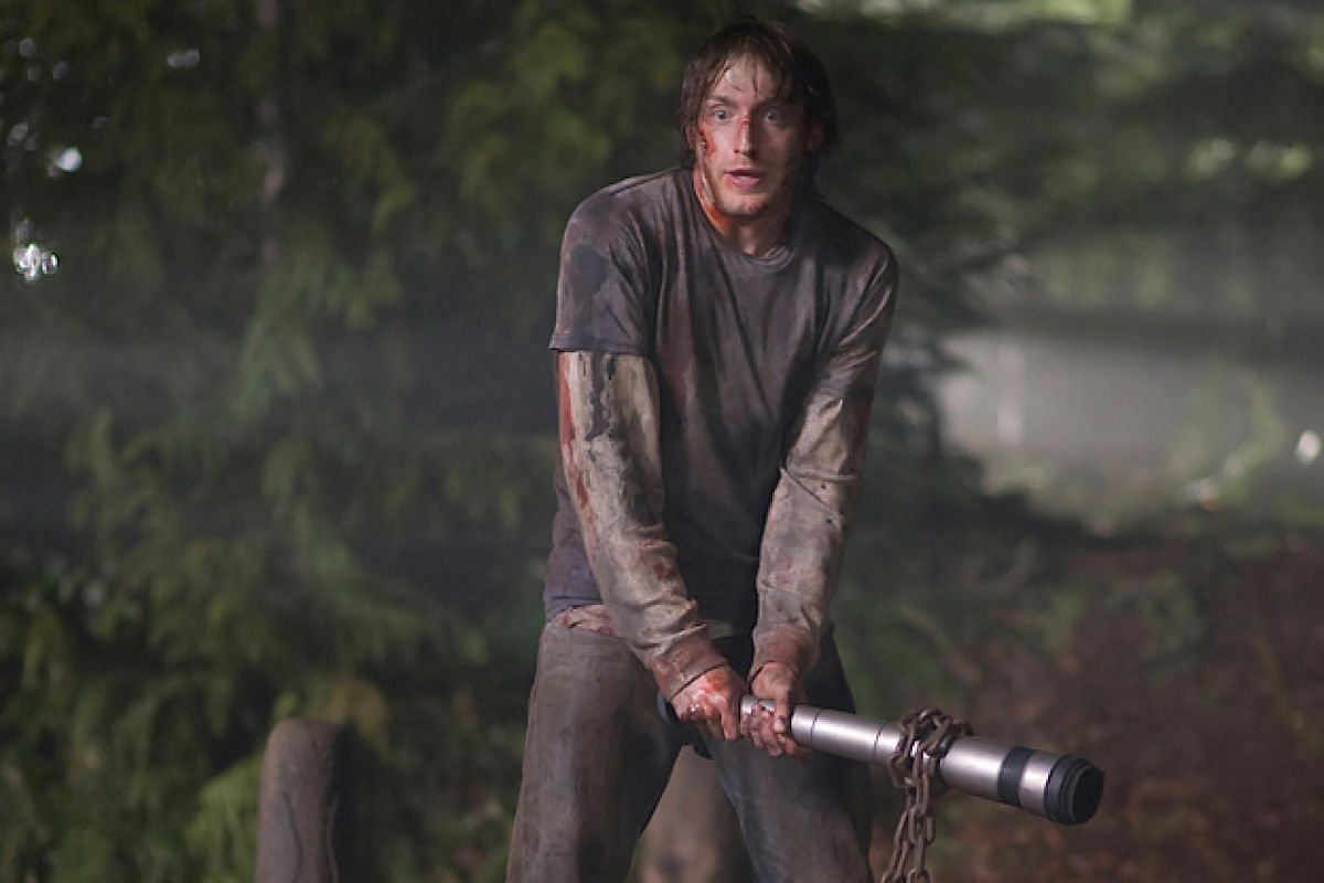 A bloodied Fran Kranz wields a telescoping bong as a weapon in The Cabin in the Woods