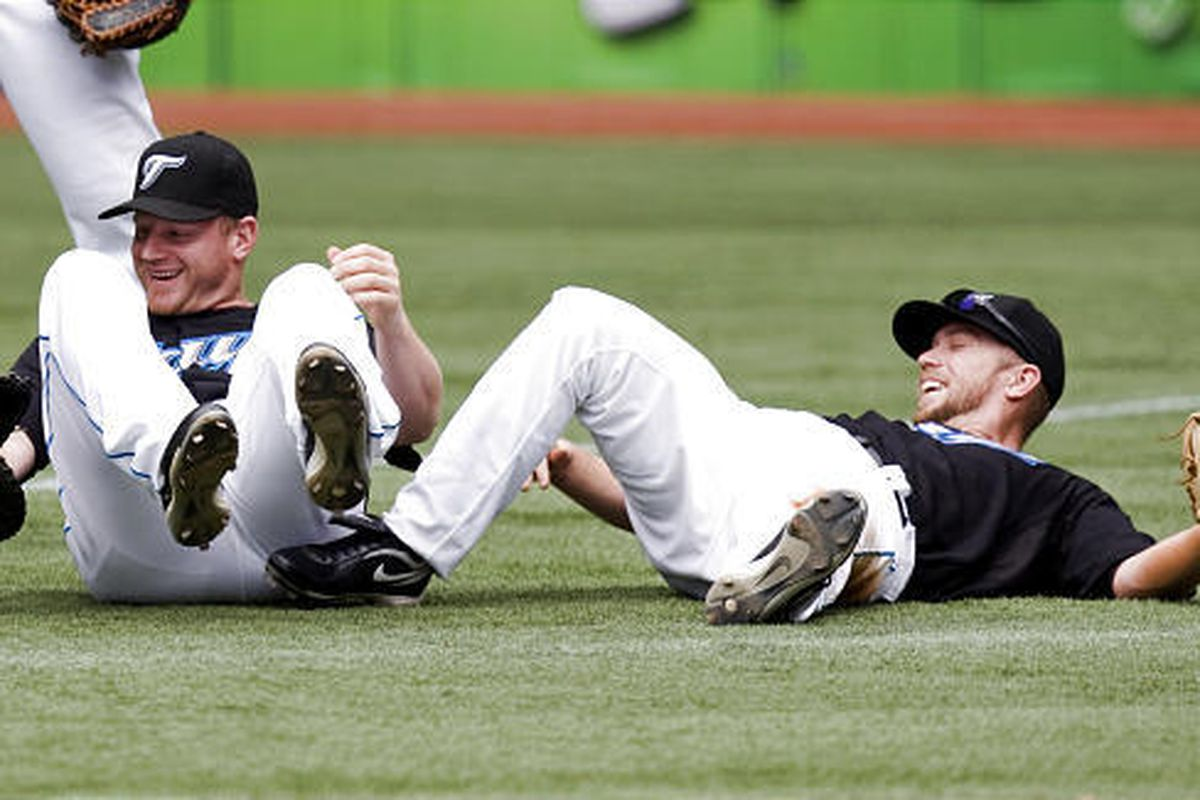 Toronto Blue Jays second baseman Aaron Hill, right, and first baseman Lyle Overbay laugh as they lie on the ground after colliding while chasing down a pop-up.