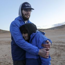 Utah Schools for the Deaf and the Blind students Benjamin Lehnig and Noah Isaac Mason hug as temperatures drop after sunset on Lone Rock Beach at Lake Powell on Friday, March 26, 2021. Lehnig, a 17-year-old from River Heights, has retinitis pigmentosa and macular edema. Mason, a 17-year-old from Manti, has retinoschisis. They are part of the the school's yacht club, which is training for the SEVENTY48, a 70-mile human-powered boat race from Tacoma to Port Townsend, Wash.