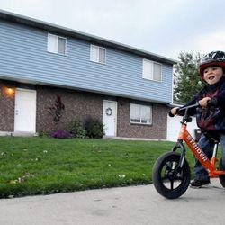 3-year-old Logan Burton rides his 'Strider' outside the Burton's home Sept. 25.