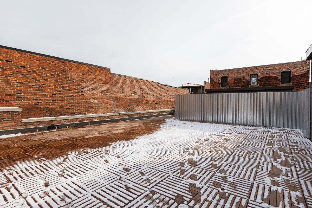 A rooftop patio dusted with snow and footprints. There's corrugated metal running along one wall.