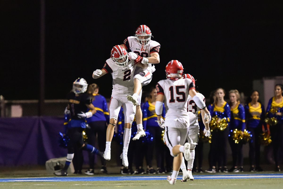 Maine South's Mike Sajenko (30) celebrates his touchdown with teammates during the game against Warren.
