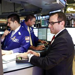 Specialist Michael A. Pistillo, right, works on the trading floor of the New York Stock Exchange shortly after the opening bell Thursday, Sept. 6, 2012. Financial markets are soaring after investors finally heard what they had been waiting for from the European Central Bank: concrete plans to support struggling countries in the region by buying government bonds. (AP Photo/David Karp)