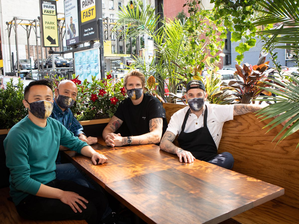 Four men sit at an outdoor wooden booth with green palm bushes surround them