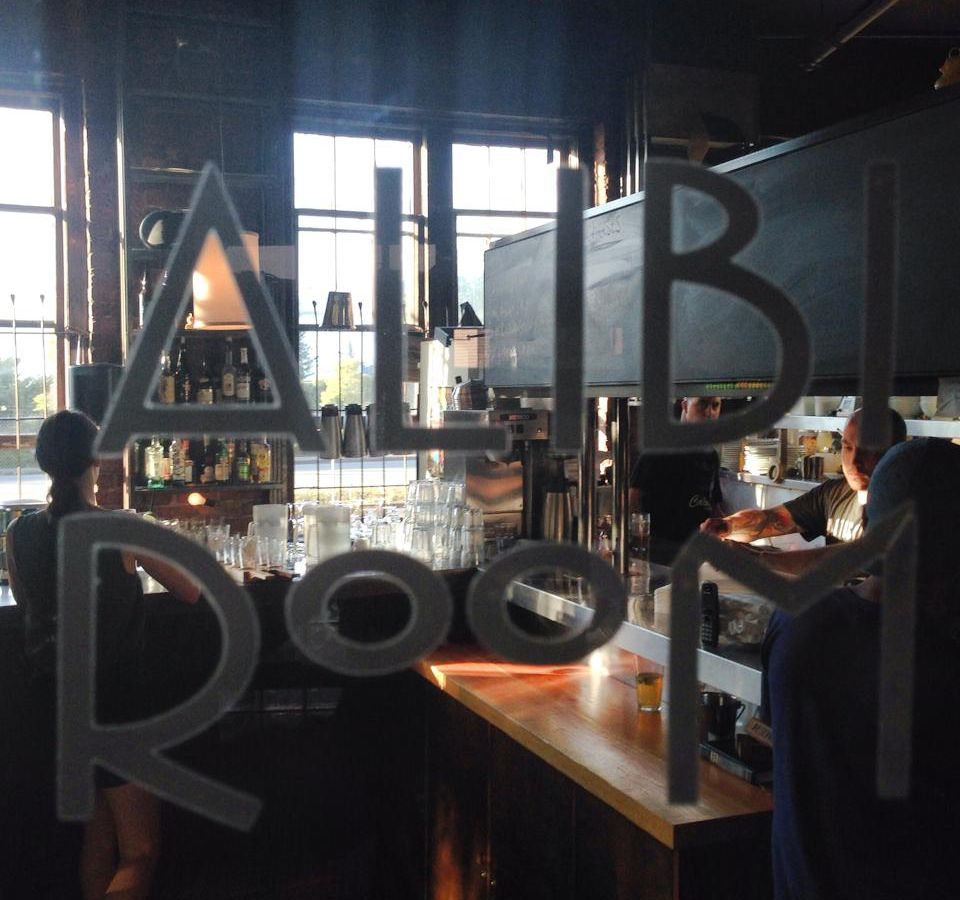 A glass door with the words Alibi Room written on the glass. Through the letters a bar is visible where a bartender works and a few patrons drink