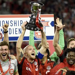 Toronto FC midfielder Michael Bradley (4) holds up the trophy as the team celebrates a win over the Montreal Impact in the Canadian championship soccer final, Tuesday, June 27, 2017, in Toronto.