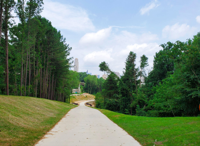 A paved trail surrounded by green hills and trees with the sky rises of buckhead beyond.
