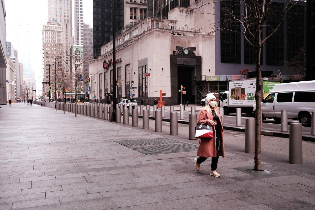 A woman walking on an empty street wearing a mask.