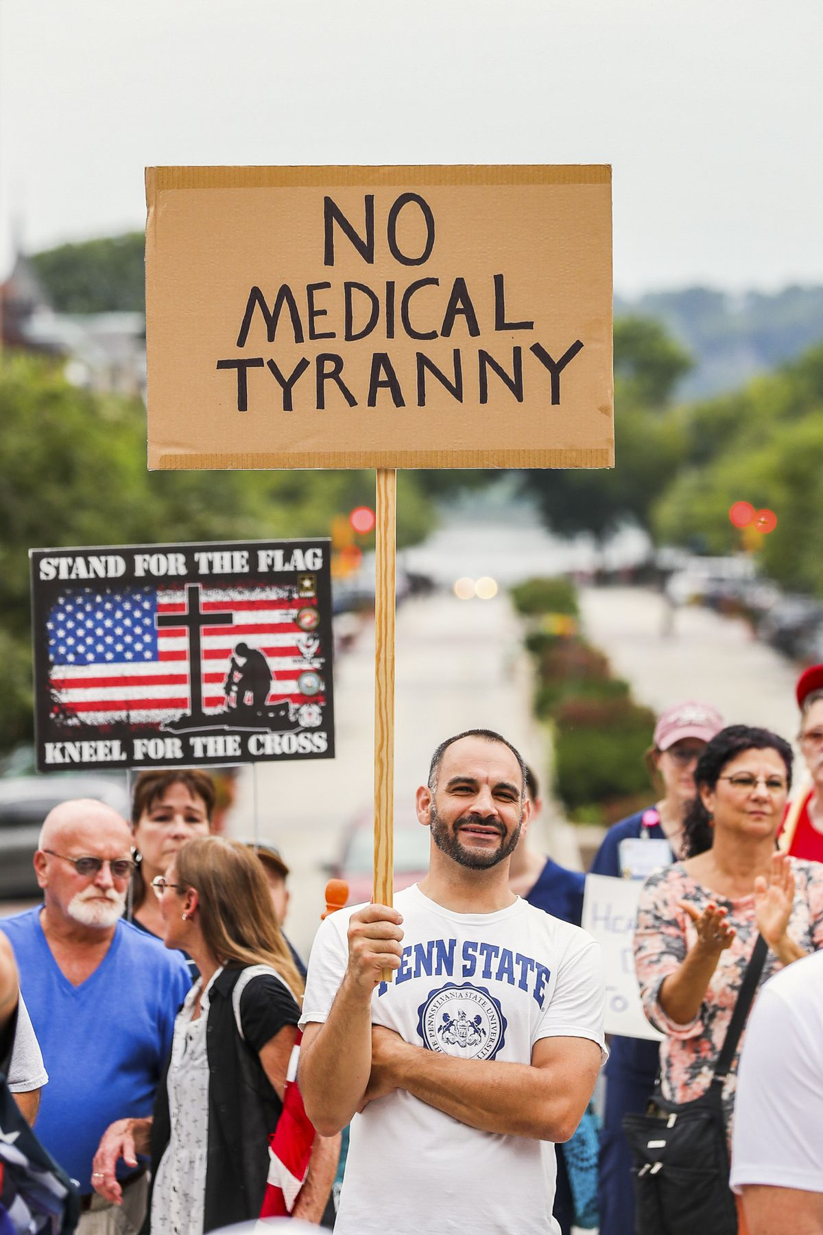 """A protester in a Penn State T-shirt holds a sign that reads, """"No medical tyranny."""""""