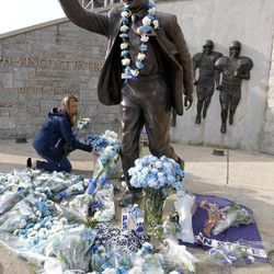 Beth Jenkins of Woodrings Floral Gardens arranges some of the more than 1400 blue and white carnations they delivered to the statue of former Penn State football coach Joe Paterno outside Beaver Stadium before the NCAA football team's annual Blue White scrimmage on Saturday, April 21, 2012, in State College, Pa.
