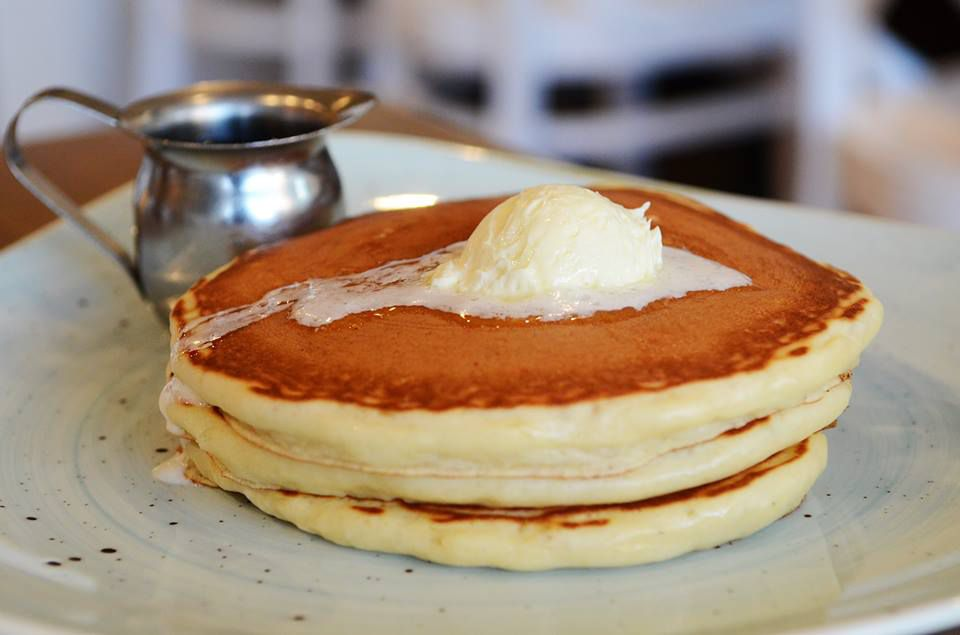 Two fluffy pancakes with golden crust are topped with a scoop of butter, melting. On the side is a small silver pitcher.