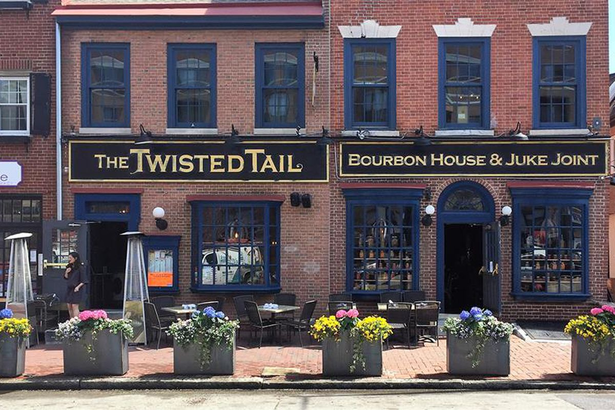 outside of brick restaurant with side that says the twisted tail bourbon house and juke joint