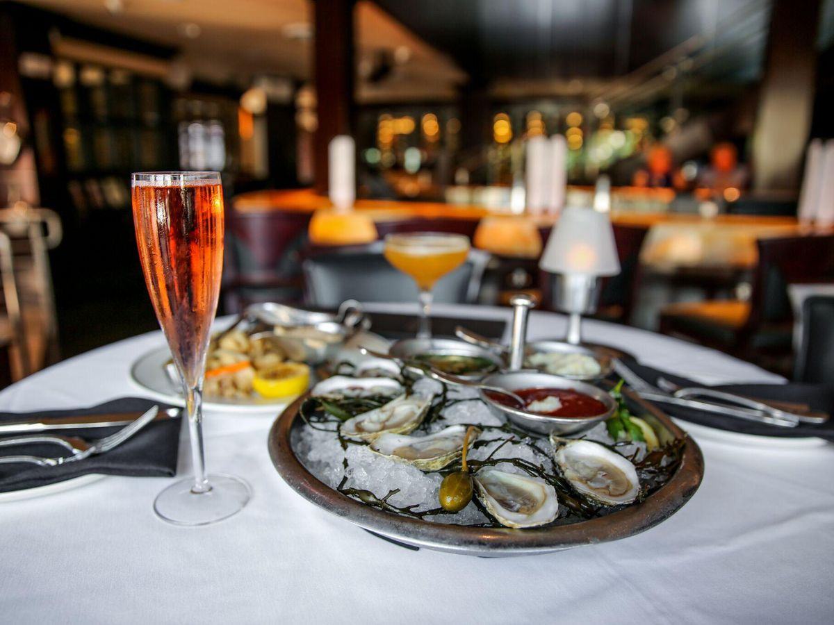 A glass of sparkling wine and a plate of oysters at Truluck's