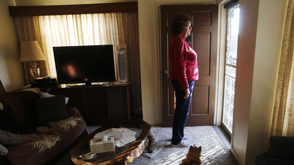 Charlotte Jensen, 77, looks out of the front door with her dog Spike at her home in Salt Lake City Nov 26, 2013.