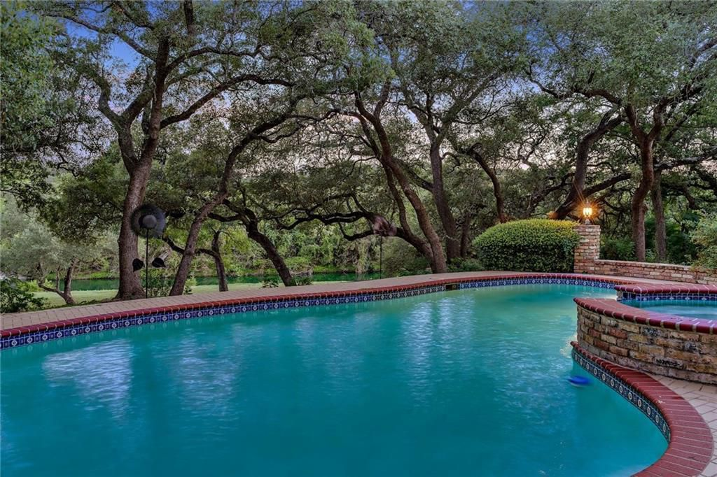A photo of a kidney shaped pool with a brick border and a connected hot tub with a screen of mature live oaks behind it.