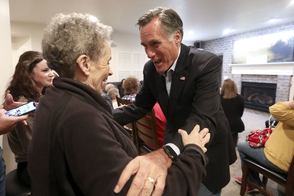 Ila Walker talks to Mitt Romney at Calvin Musselman's home in West Haven on Monday, Oct. 8, 2018.