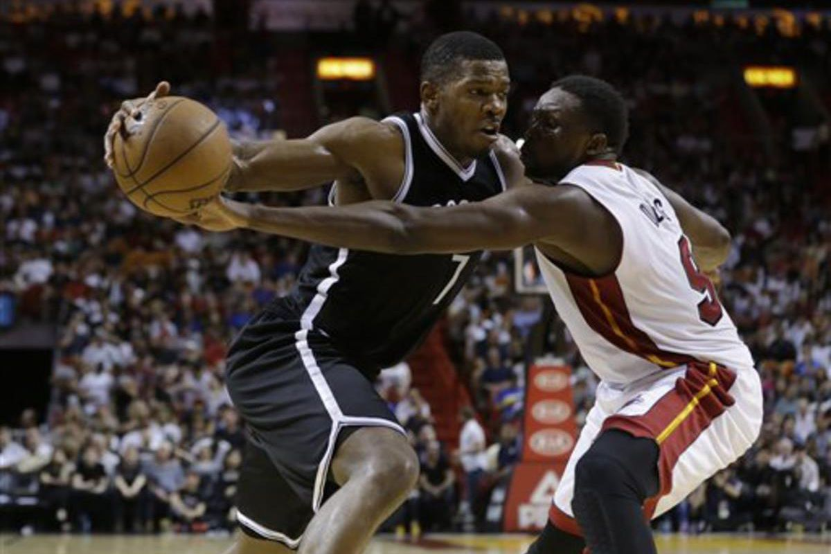 Brooklyn Nets forward Joe Johnson (7) drives to the basket as Miami Heat forward Luol Deng (9) defends during the second half of an NBA basketball game, Sunday, Jan. 4, 2015, in Miami. The Heat defeated the Nets 88-84.