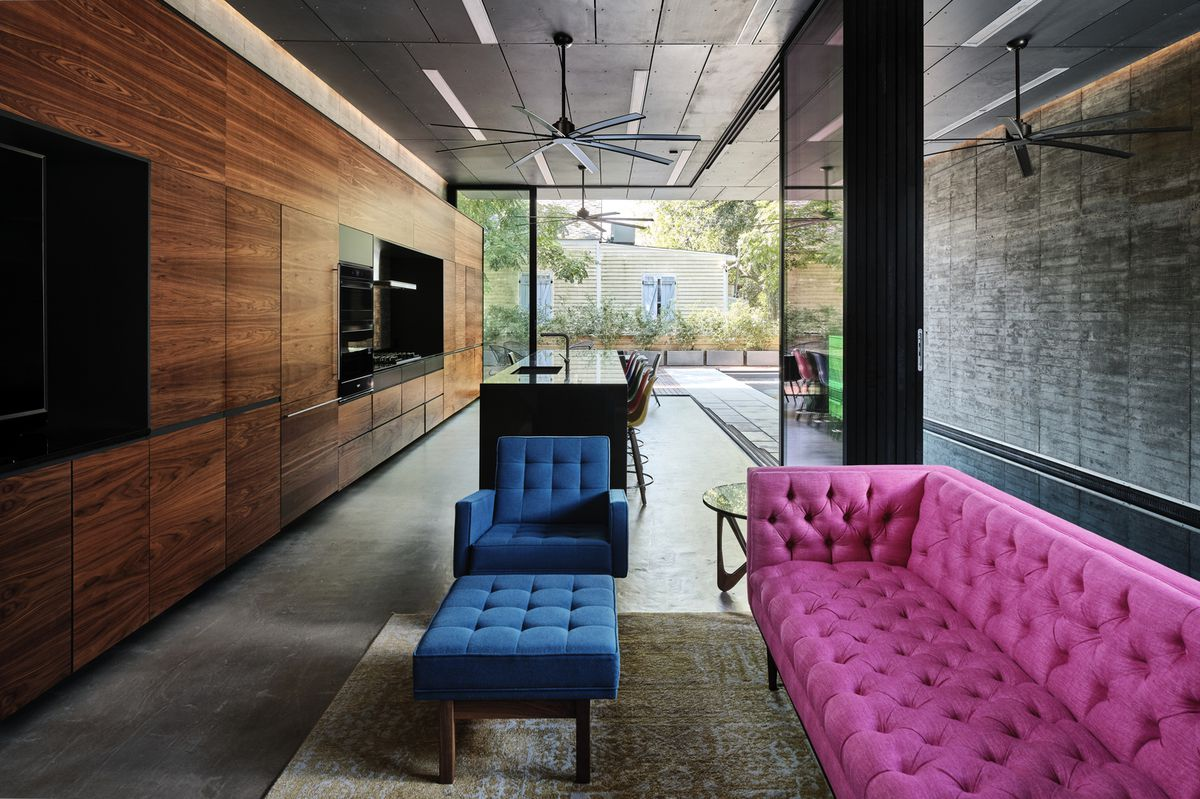 Bright pink couch in modern, concrete-floored living room