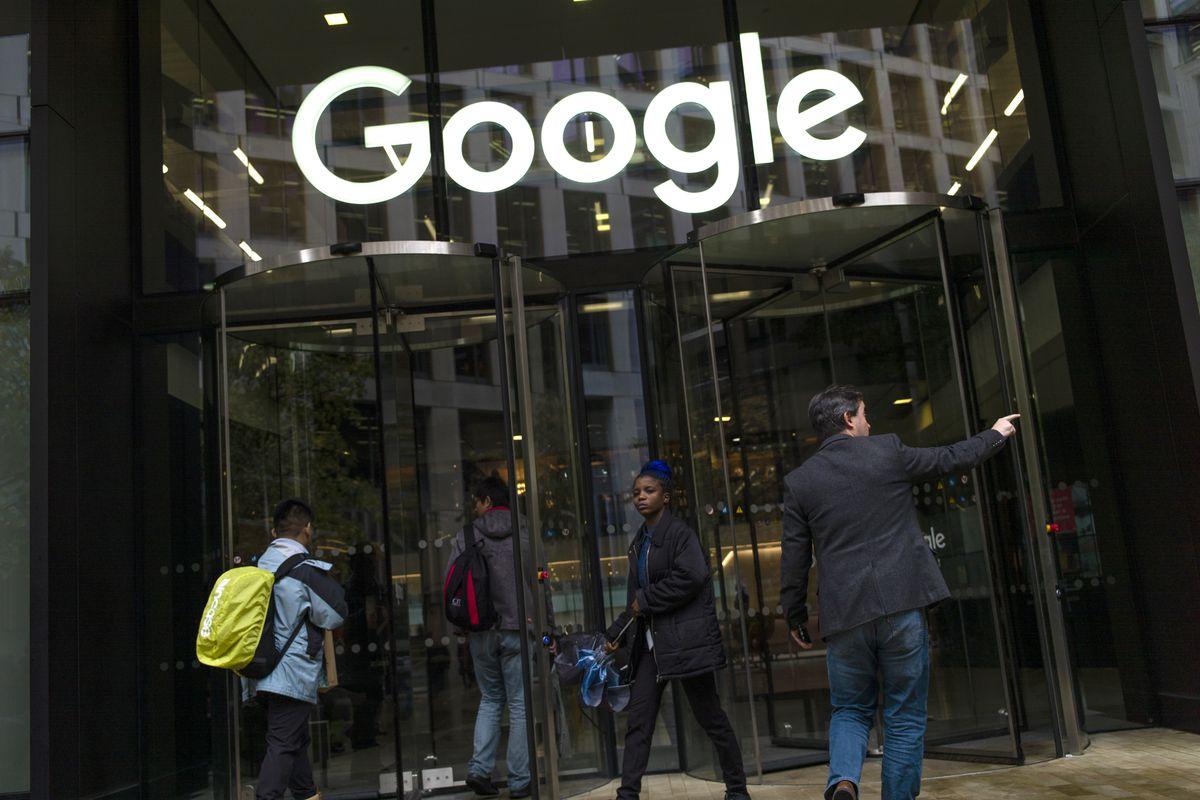 "Google employees walking through a glass door under a sign reading ""Google."""
