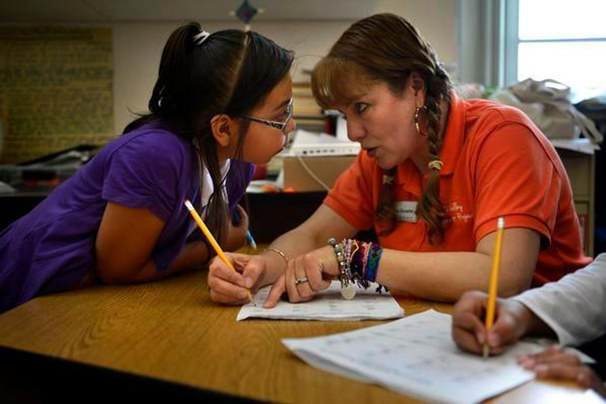 A parent mentor helps a student with a math problem at Crystal River Elementary School in Carbondale in 2013.