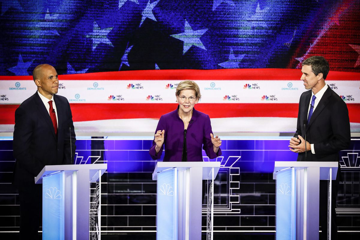 Sen. Elizabeth Warren (D-MA) speaks as Sen. Cory Booker (L) (D-NJ) and former Texas congressman Beto O'Rourke look on during the first night of the Democratic presidential debate on June 26, 2019 in Miami, Florida.