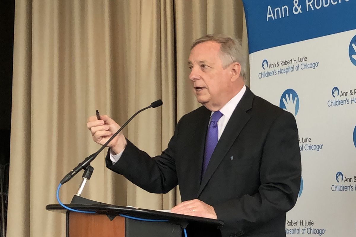 Sen. Dick Durbin, D-Ill., holds up a vaping device during a news conference