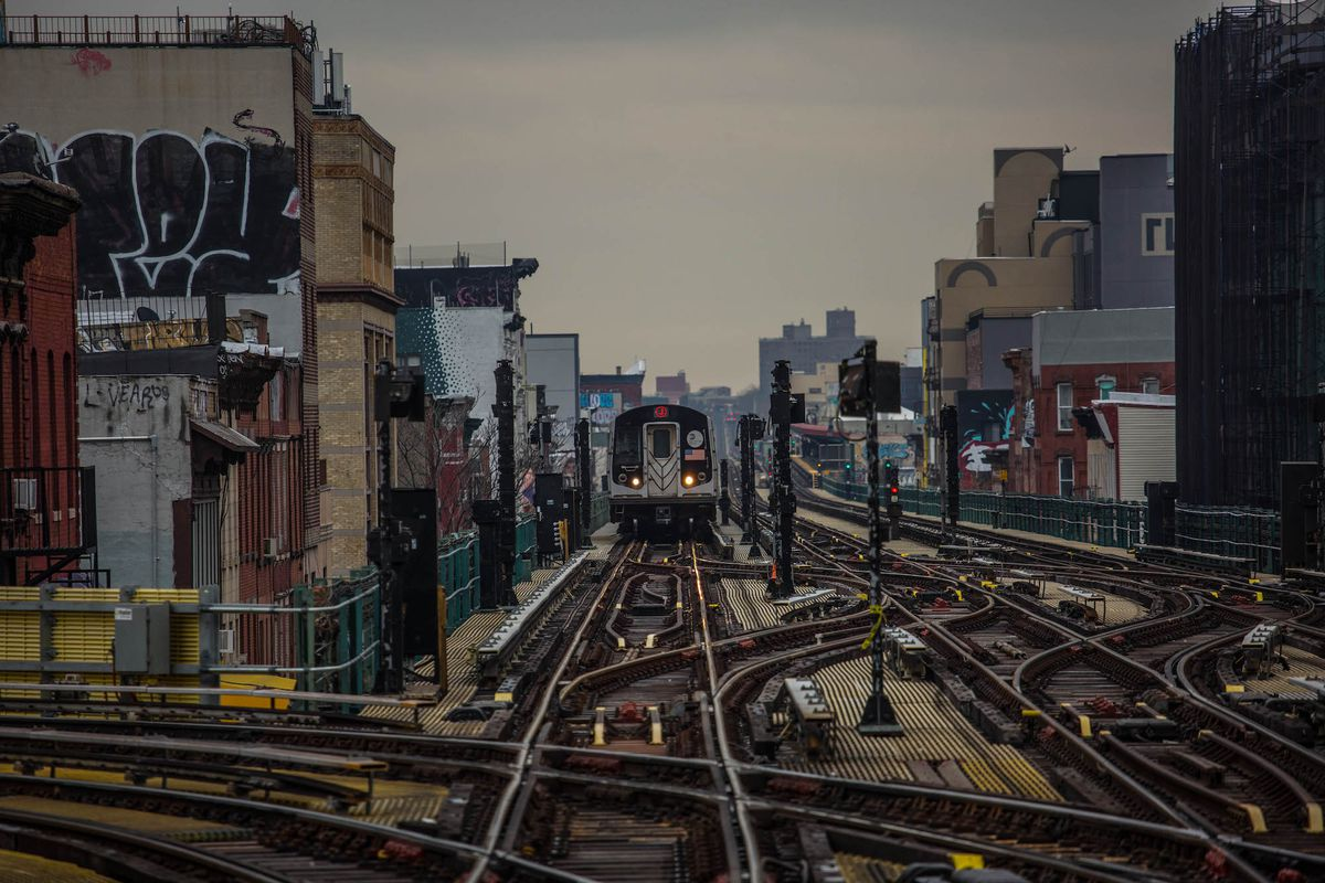 On a gloomy day, a New York City subway train travels on elevated, snaking tracks adjacent to old buildings with graffiti