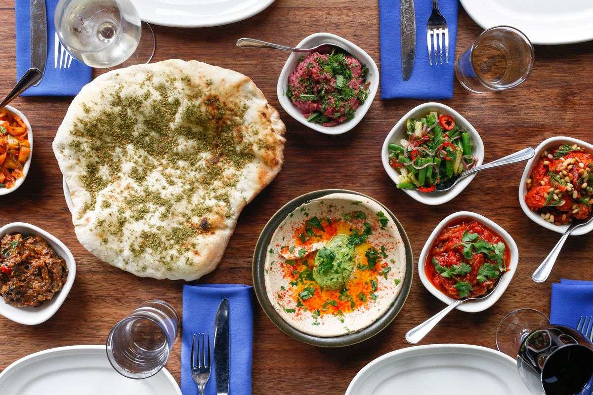 a plate of hummus, sauces, pita, and blue napkins with fork and knives at the restaurant Zahav