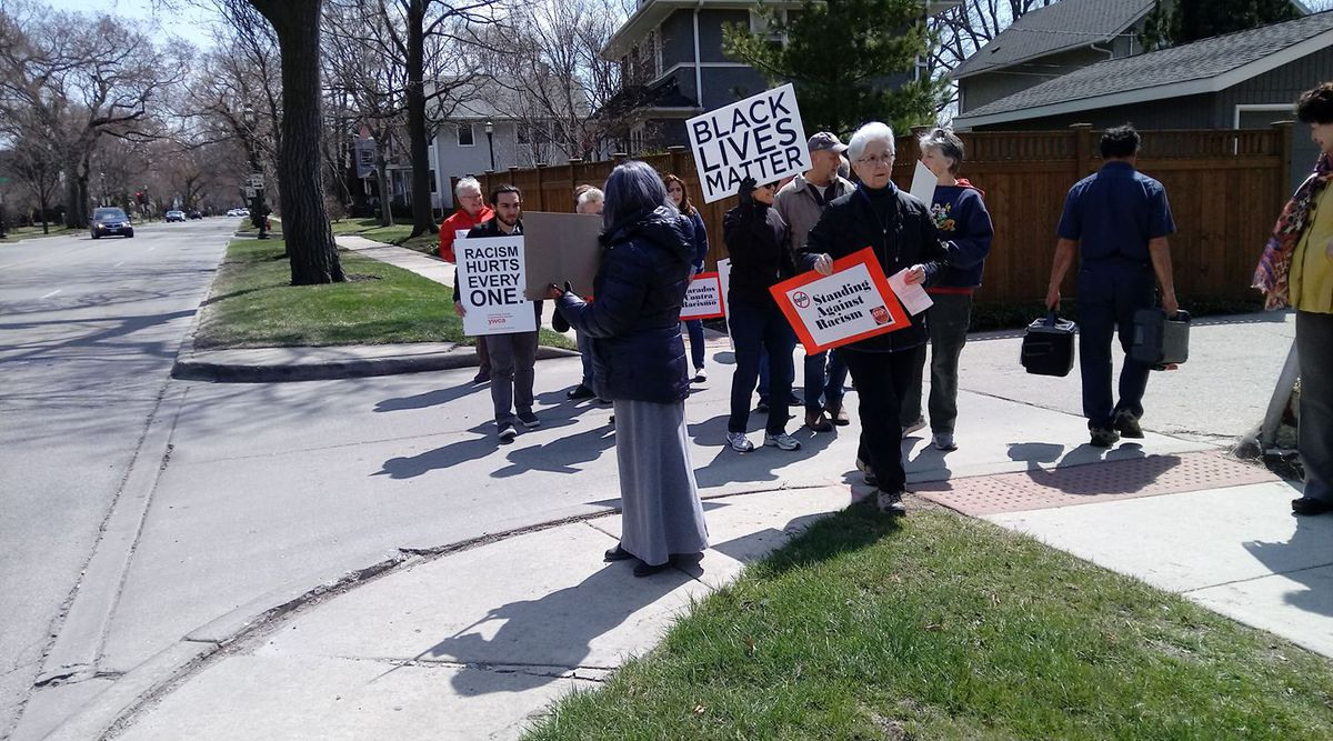"""Marion Flynn, in the foreground, holds a """"Standing Against Racism"""" sign at a protest."""