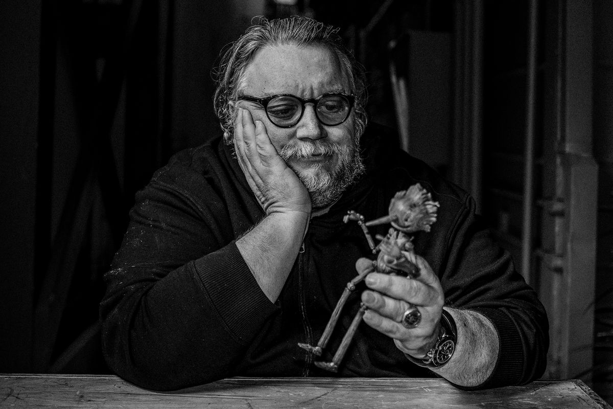 Guillermo del Toro sits with Pinocchio puppet in his workshop for Netflix movie