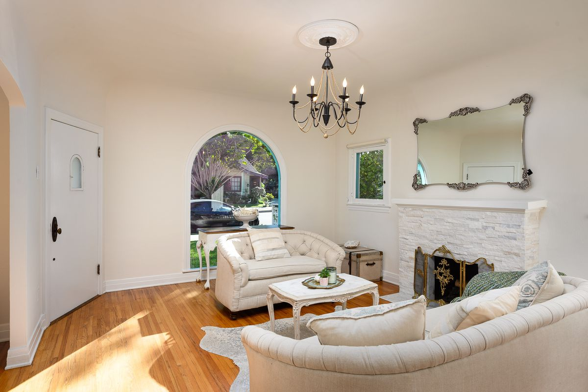A living room with filtered sunlight, a large arched window, hardwood floors, and a white-washed stone fireplace.