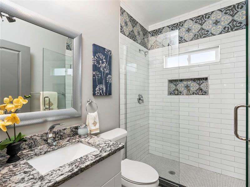 A white bathroom with wild tiles.