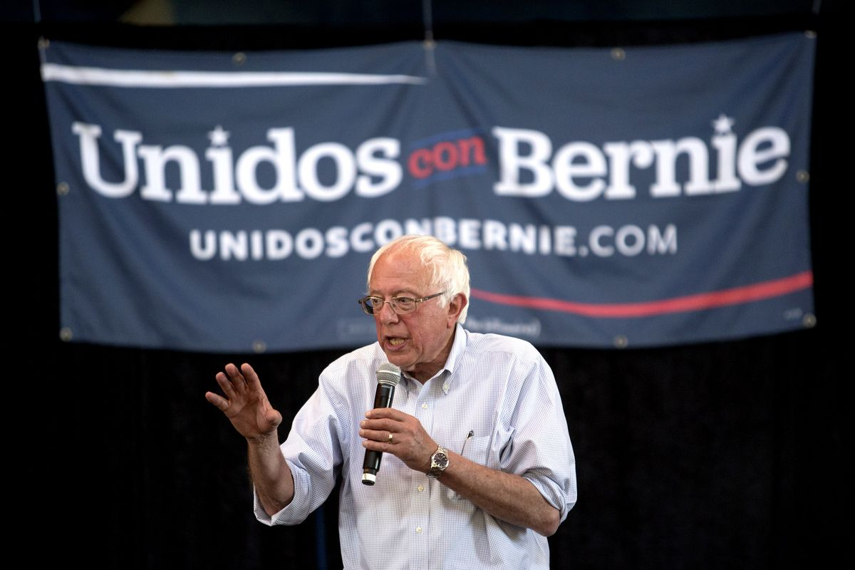 """Bernie Sanders in front of a sign in Spanish saying """"Unidos con Bernie."""""""