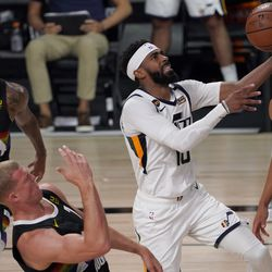 Utah Jazz's Mike Conley (10) goes up for a shot between the defense of Denver Nuggets' Torrey Craig (3), Mason Plumlee (7) and Michael Porter Jr. (1) during the second half an NBA first round playoff basketball game, Tuesday, Sept. 1, 2020, in Lake Buena Vista, Fla.