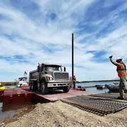 A dump truck unloads from a barge at Willard Bay on Thursday, June 9, 2016. The Utah Division of Wildlife Resources used the barge and dump trucks to place boulders in Willard Bay to enhance fish habitat.