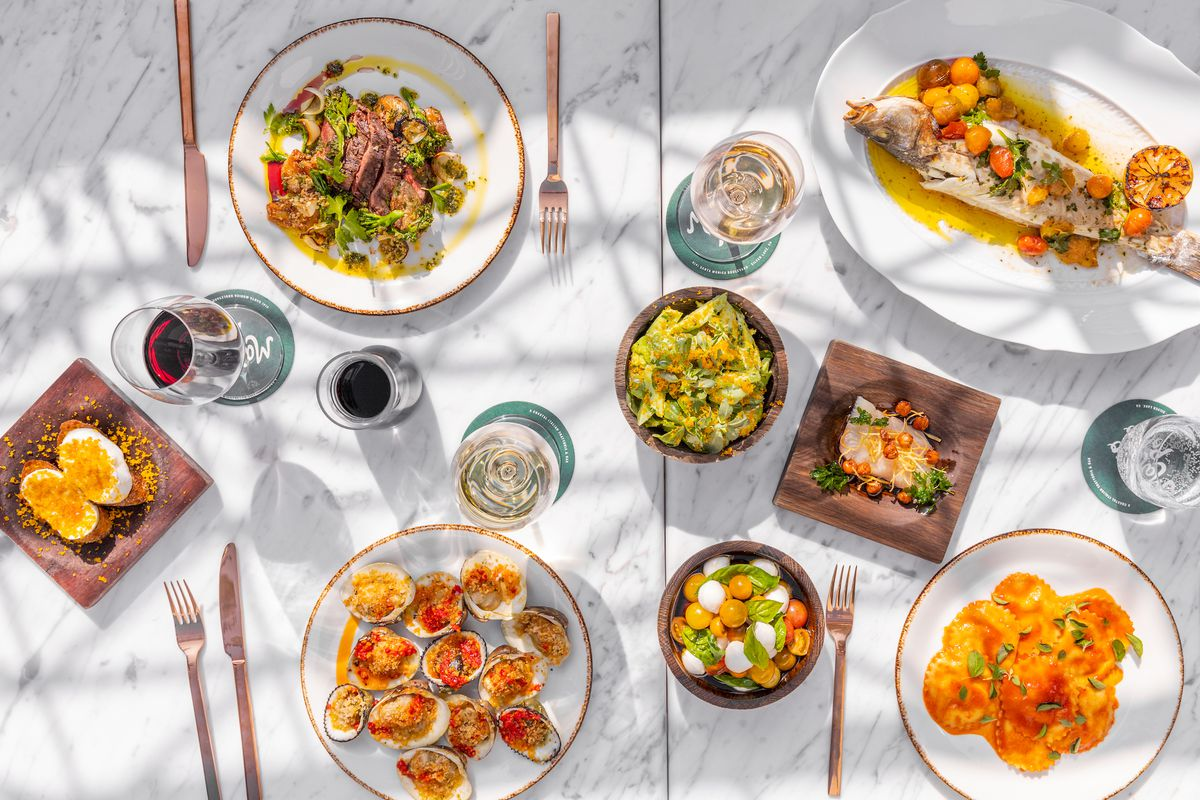 An array of coastal Italian dishes on a sunny marble table, including seafood and pastas.