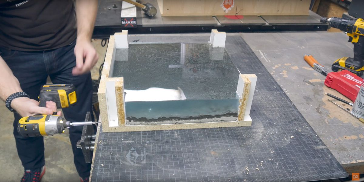 Pessoa usando uma lixadeira orbital para separar a mesa do rio do molde.