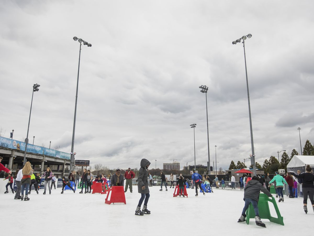 Ice skaters on a ice skating rink.