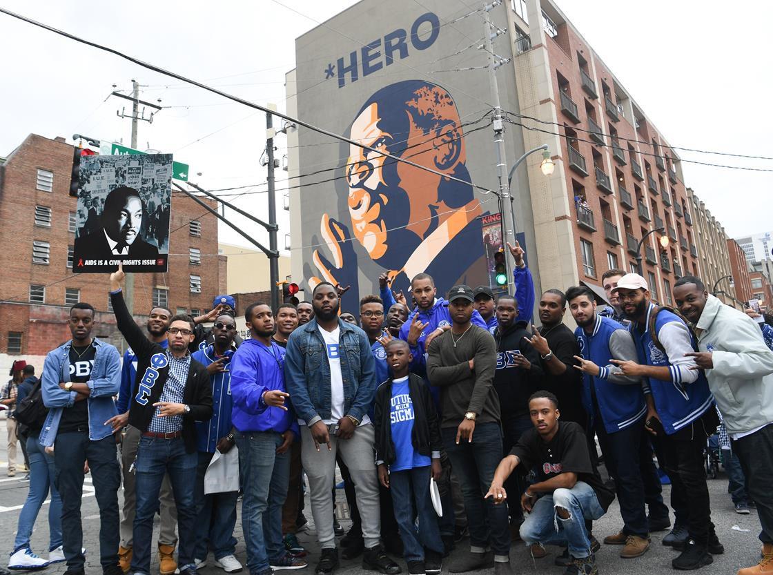 People standing in front of John Lewis hero mural
