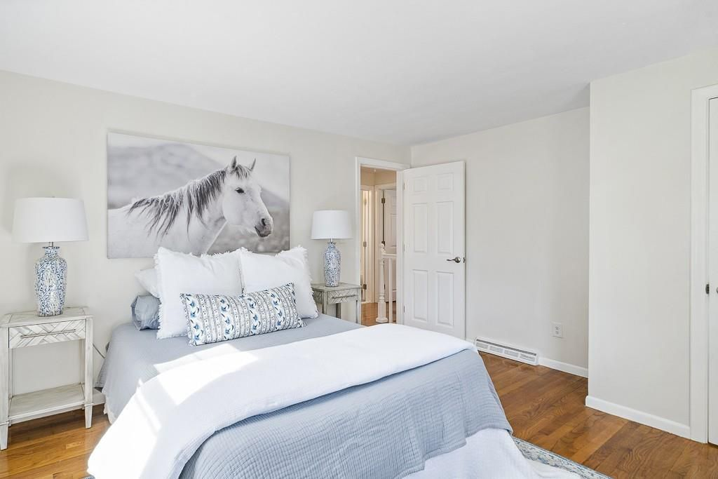 A bedroom with a bed beneath a painting of a horse.