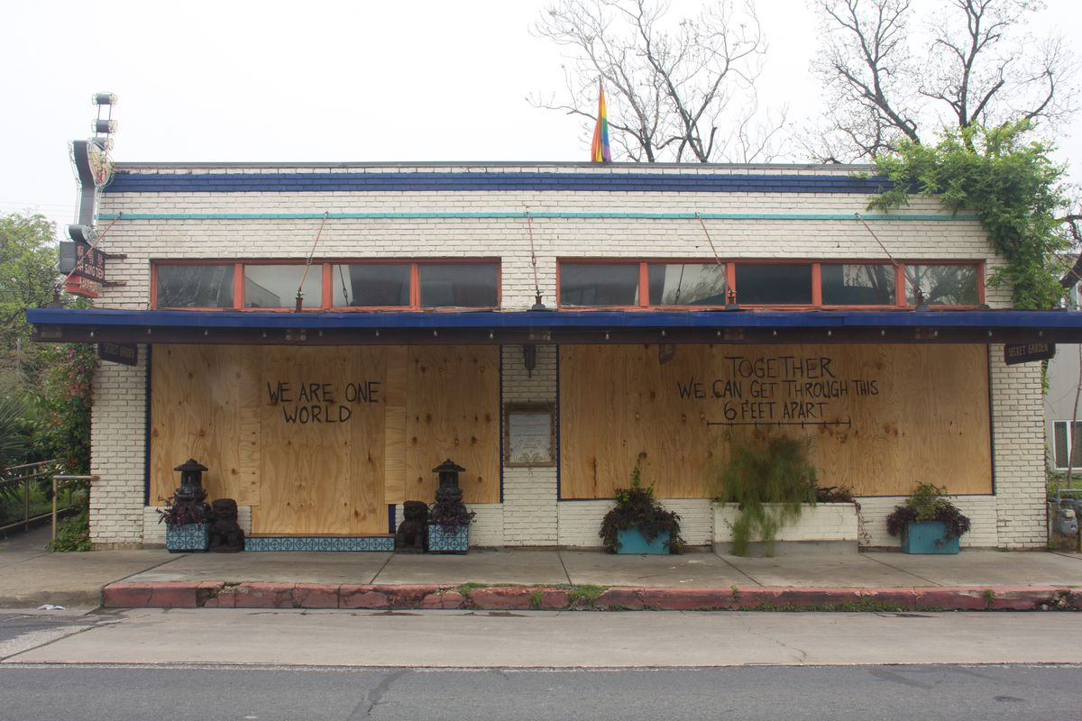 """East Austin bar Ah Sing Den boarded up its windows and wrote """"We Are One World"""" and """"Together We Can Get Through This 6 Feet Apart"""""""