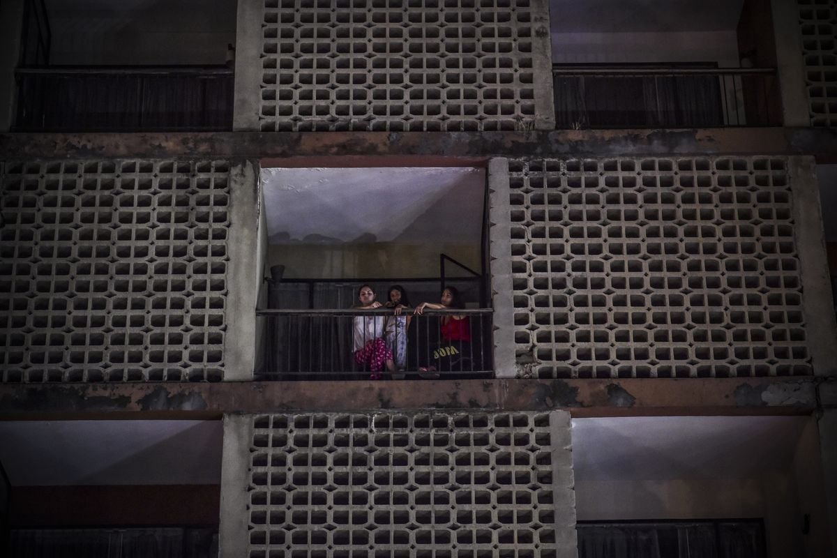 Women look from an apartment building during a power cut in Caracas on March 7, 2019.