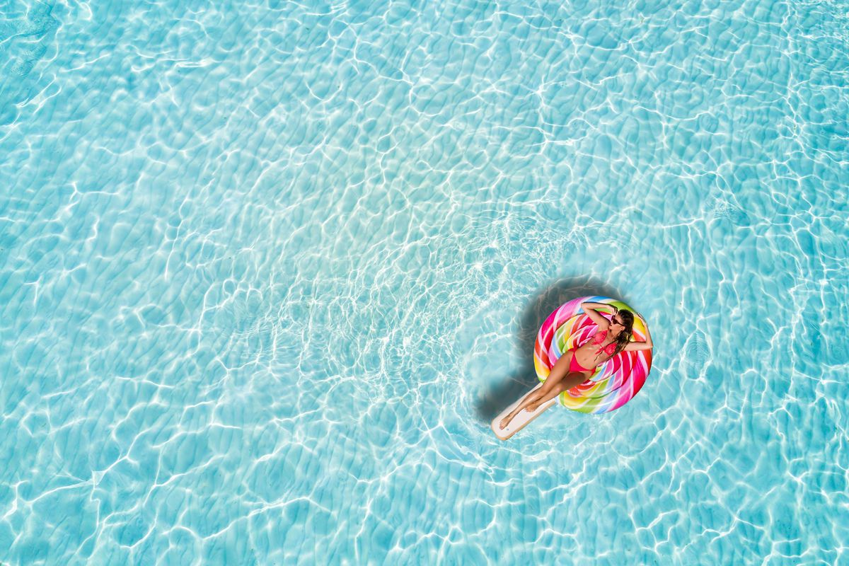 A person on a floatie in an expanse of pool water.